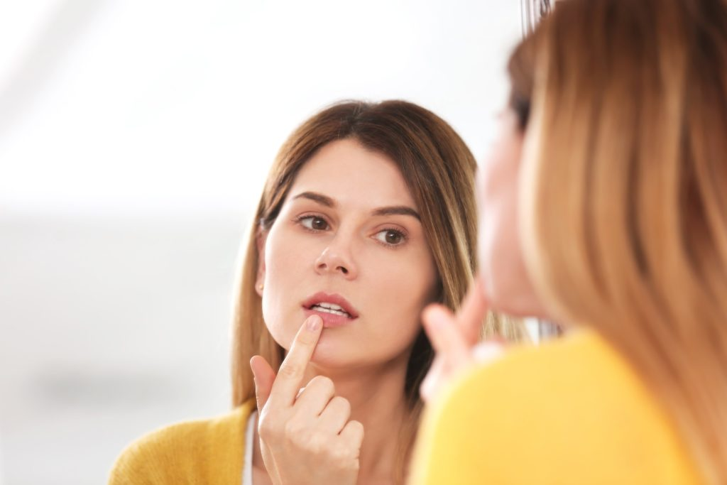 A woman looking at her reflection in a mirror and closely examining her teeth