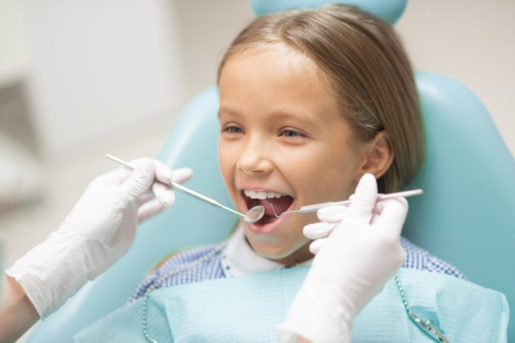 A child in a dental chair receiving a dental checkup
