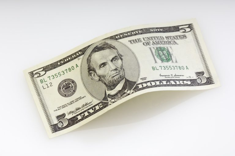 A five dollar bill on a gray background