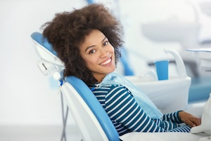 Woman with brown hair sitting in a dental exam chair while looking over her shoulder and smiling