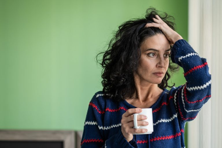 Woman looking stressed holding a coffee mug