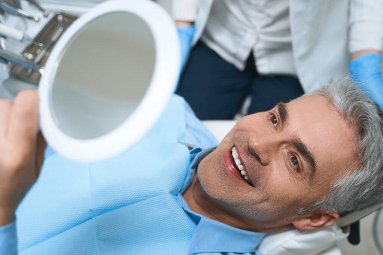 A male dental patient lays back in a dental exam chair and admires his smile in a handheld mirror