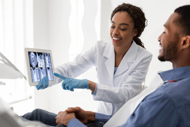 A female dentist holds a dental x-ray while explaining root canal steps to a patient