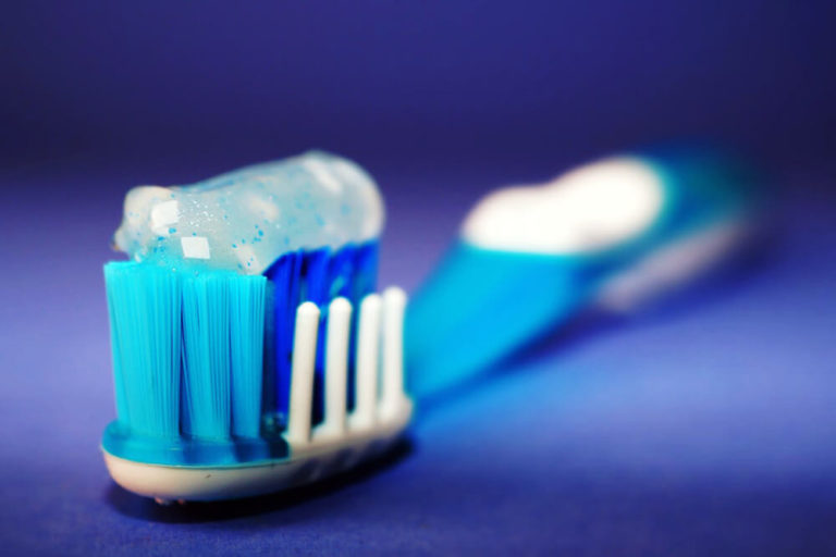 A toothbrush with toothpaste on the bristles where the head of the toothbrush is in focus