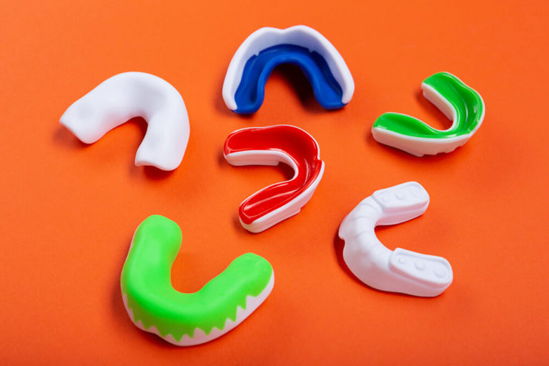 Six sports and teeth grinding mouth guards sitting on an orange background