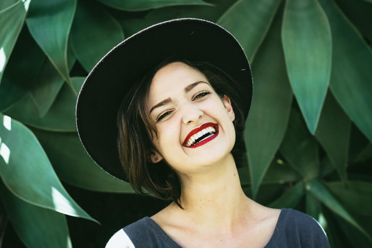 A woman in a large hat smiles in front of a backdrop of green leaves showing off brilliant white teeth